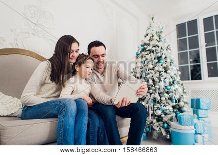 selfie in Christmas. happy family father dad mom playing with baby boy and photographed on a tablet pc.