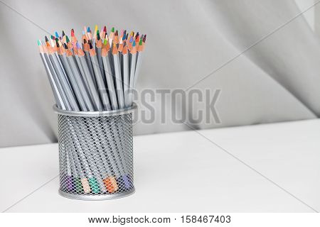 Gray metal pen pot basket with colored pencil on gray background white table
