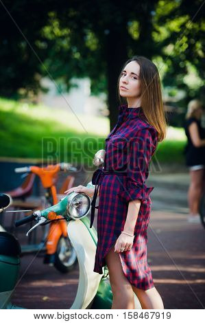 Fashion woman in checkered dress posing and pulling her hair near scooter over summer park background.