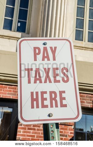 Easy to see sign in front of the building where you go to pay your taxes. No excuses with a sign like this!
