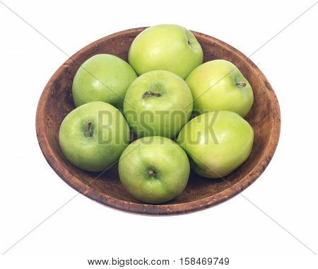 Green organic granny smith apples in wooden bowl isolated on white background