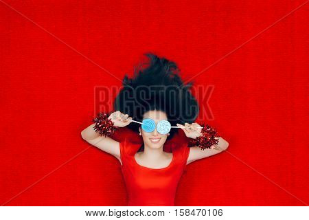 Smiling Christmas Girl Holding Lollipops on Red Background