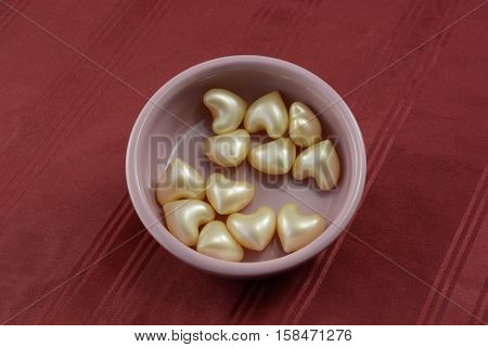Heart shaped beauty bath oil beads in pink ceramic dish