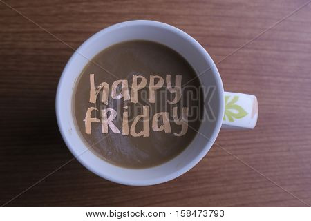 Happy friday./ Inscription happy friday in a cup of coffee and wooden background