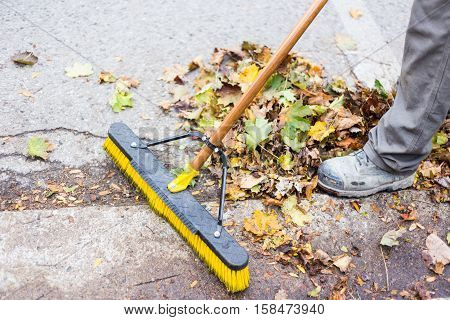 A home owner or worker doing the annual fall leaf clean up from the gutter and sidewalks