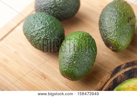 Two Avocados on wooden cutting board table