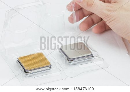 Man's hand opening a box with a CPU. Next to it is another open box with a processor. The second processor is turned upside-down. Isolated on white background.