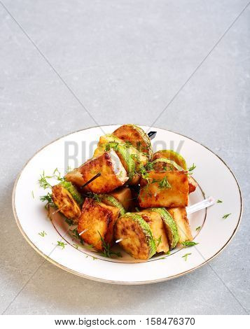Zucchini and panir snacks on sticks on plate