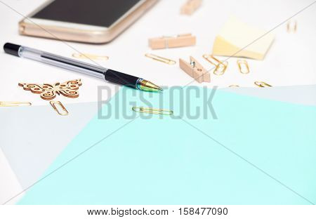 Top view of white and olive blank of paper sheet gold stationery items several drawing tools decorated with wooden butterfly