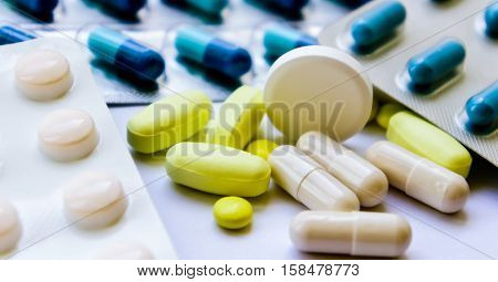 medical pills white, yellow and blue, small and one big round on the right of the photo, medicines in packing and scattered on a white table, yellow oblong heap lie,