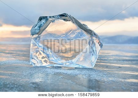 Transparent ice block at frozen surface with reflection and sunset sky. Winter Baikal lake