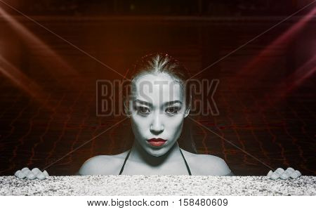Closeup face of sexy sensual Asian woman with wet hair standing in the swimming pool and looking into the camera during summer evening over red lights reflections background