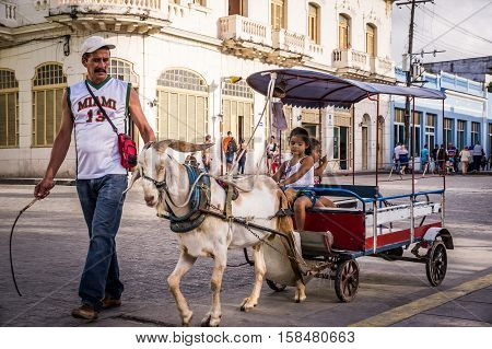 Santa Clara, Cuba on December 26, 2016: A Cuban guy with a whip is guiding a goat that is pulling a small carriage. In the back of the carriage two young girls are enjoying the ride.