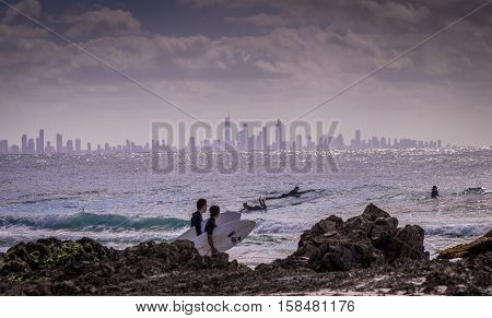 Surfers Paradise, Australia on August 16, 2016: Surfers enjoying the waves at snapper rocks with the skyline of Surfers paradise in the background