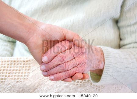 Young holding senior woman