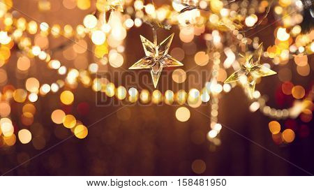 Christmas and New Year glowing Background with Holiday Decoration garland, tinsel and stars. Abstract Blurred Bokeh Holiday Backdrop. Blinking Garland. Christmas Tree Lights Twinkling