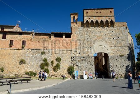 San Gimignano Italy - September 6 2016: Defensive walls and gate in San Gimignano city in Tuscany Italy. Unidentified people visible.