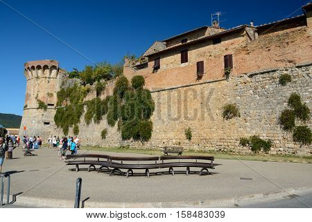 San Gimignano Italy - September 6 2016: Defensive walls and bench in San Gimignano city in Tuscany Italy. Unidentified people visible.