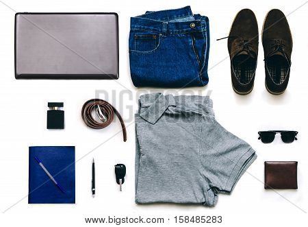 Outfit of clothes young man with vintage blue jeans, grew shirt, brown suede shoes, clubmaster sunglasses, purse and other on the white background
