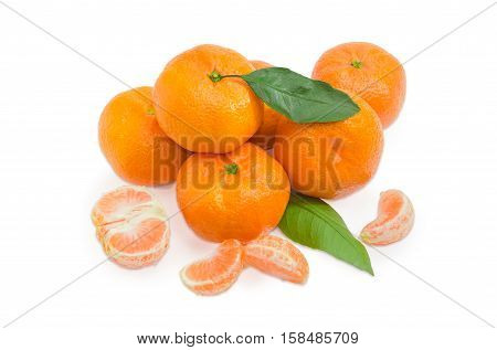 Pile of a fresh mandarin oranges with leaf and several segment of peeled mandarine on a light background