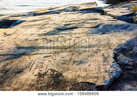 Attraction of Karelia is Onega petroglyphs on the sunset - prehistoric rock engravings (4th-2nd millennia BC) carved on the granite shore of the lake on the cape Besov Nos.