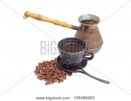 Old copper coffee pot with freshly brewed coffee coffee in black ceramic cup with saucer and spoon and pile of roasted coffee beans on a light background