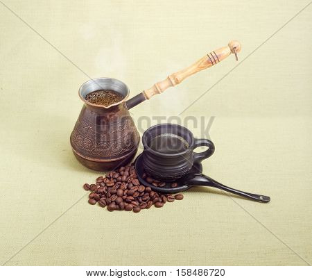 Old copper coffee pot with freshly brewed coffee coffee in black ceramic cup with saucer and spoon and pile of roasted coffee beans on a hessian