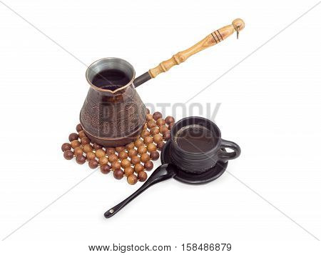 Freshly brewed black Turkish coffee in a old copper coffee pot on trivet made of balls of juniper wood and in black ceramic cup on a light background