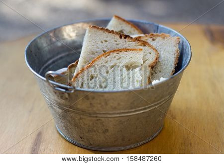 close up of aluminum bucket with handles and pieces of freshly cut bread standing on wooden board
