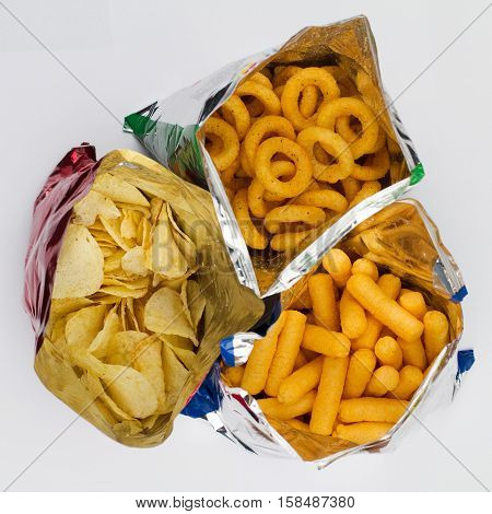 top view of three open bags of chips of different sizes colors and textures