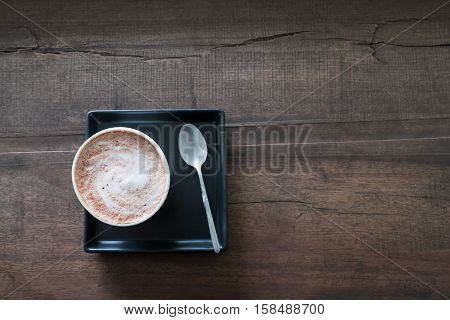 Hot chocolate with whipped cream a flavor hot drink on wood rustic table top view of cocoa in a mug vintage tone.