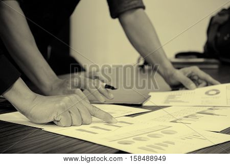 Image of male hand pointing at business document during discussion at meeting business man point on a work table with point business chart vintage effect