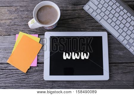 Tablet pc with www and a cup of coffee on wooden background