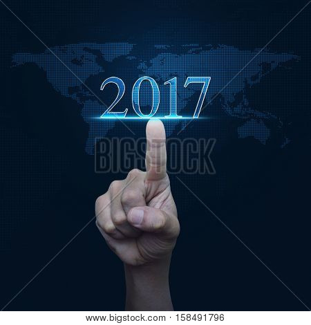 Hand pressing 2017 text over digital world map blue background Happy new year concept Elements of this image furnished by NASA