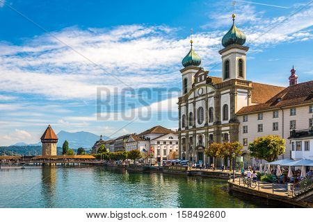 LUZERN,SWITZERLAND - SEPTEMBER 3,2016 - View at the Chapel bridge over Reuss river and Jesuit church in Luzern. Luzern is a city in central Switzerland.