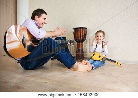 Young Father And Little Son Playing Guitar
