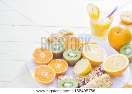 The concept of healthy breakfast orange juice fruit and cereal bars clouse up on wooden table with copy space. Good morning still life. Wonderful breakfast in the bright colors energy boost for the day.