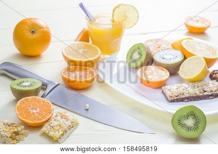 The concept of a healthy breakfast orange juice fruit and cereal bars on the yellow wooden table. Good morning still life. Wonderful breakfast in the bright colors energy boost for the day.