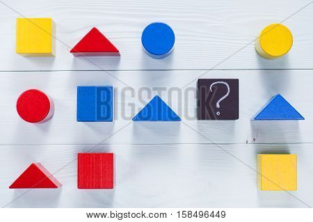IQ test. Choose correct answer. Logical tasks composed of geometric wooden shapes. Children's educational logical task flat lay.