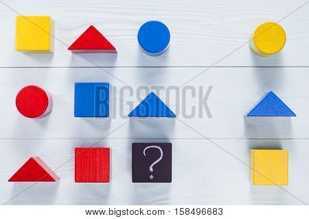 IQ test. Choose correct answer. Logical tasks composed of geometric wooden shapes. Children's educational logical task flat lay. poster