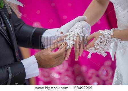 a man putting the wedding ring on his brides finger in holy matrimony