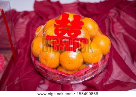 Pile stack of bright orange gift with shuang xi double happiness symbol