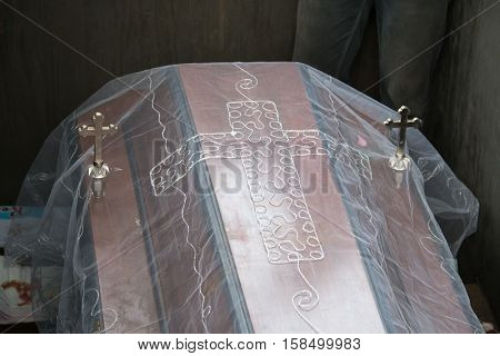Dark wooden coffin with Jesus crucifix fabric