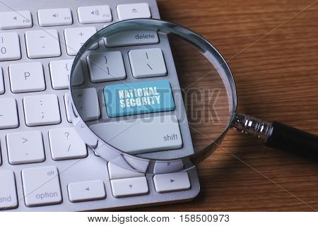 Security concept: computer keyboard with word National Security selected focus on enter button background