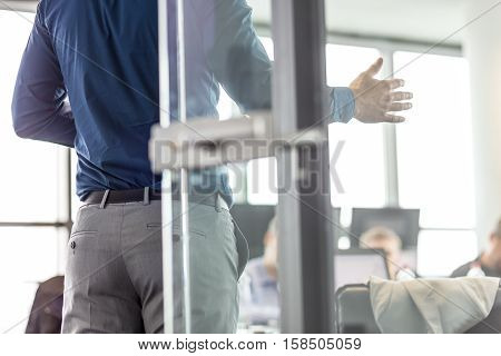 Business man making a presentation at office. Business executive delivering a presentation to his colleagues during meeting or business training. View through glass. Business and entrepreneurship.