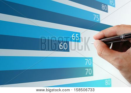 Close up Businessman hand holding pen pointing chart on laptop screen.