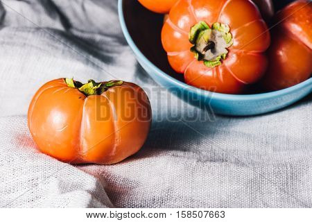 One Persimmon Near the Bowl of Persimmons on White Cloth
