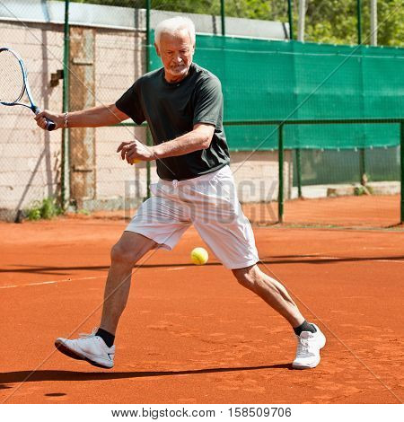 Active senior man playing tennis , toned image, outdoors