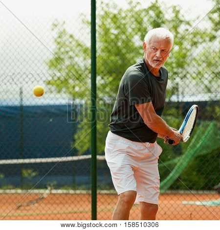 Senior male tennis player, toned image, outdoors