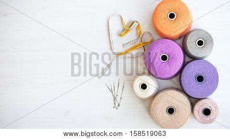 skeins of wool on background gray wood tape measure needles